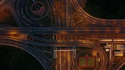 Overhead flyover the complex road junction highway. Night Light, Thailand road, sunset. High altitude drone flight. Ultrahd 4K.
