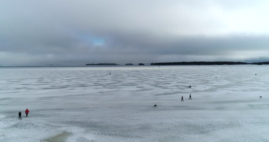 People walking on ice, Cinema 4k aerial view of people on ice, infront Haukilahti coast, on a cloudy day, at the baltic sea, in Haukilahti, Espoo, Finland