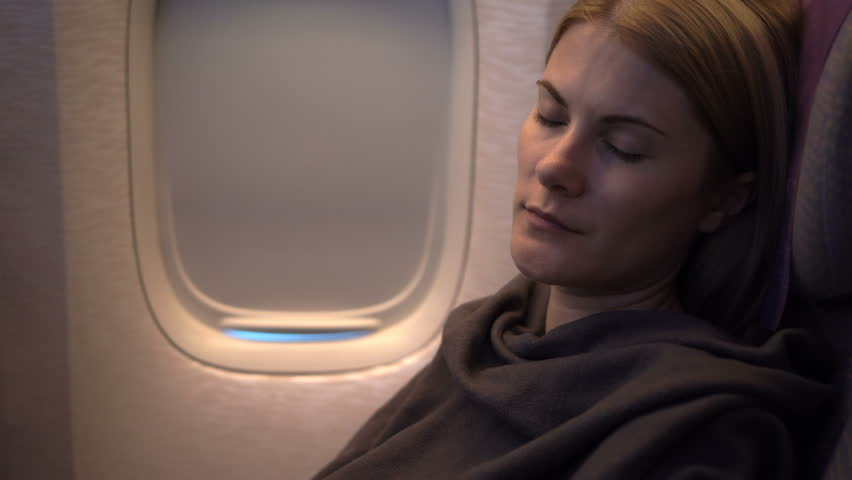 Beautiful attractive young woman sleeping near airplane window. Long distance flight night.