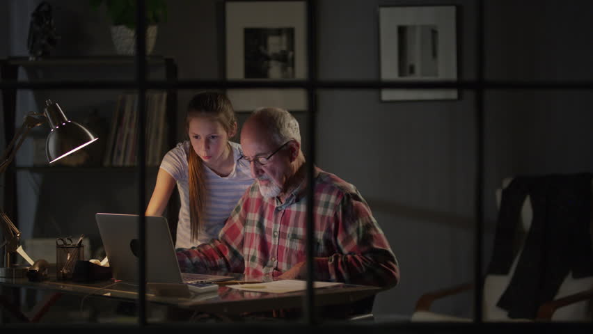 Medium zoom in shot of girl helping grandfather with laptop / Cedar Hills, Utah, United States