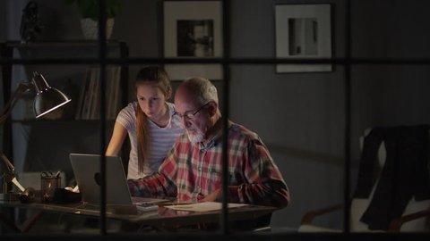 Medium zoom in shot of girl helping grandfather with laptop / Cedar Hills, Utah, United States