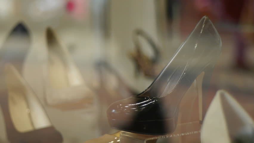 Part of a shop window shoe display. People walking past are reflected in the glass. The display is sharp. The people are blurred.