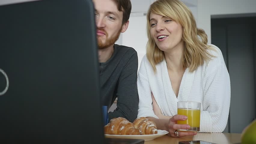 Young couple talking over laptop during breakfast in the kitchen.