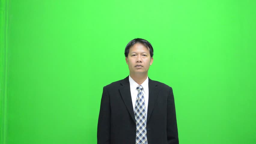 Asia businessman in front of a green screen making hand gestures in a virtual business environment