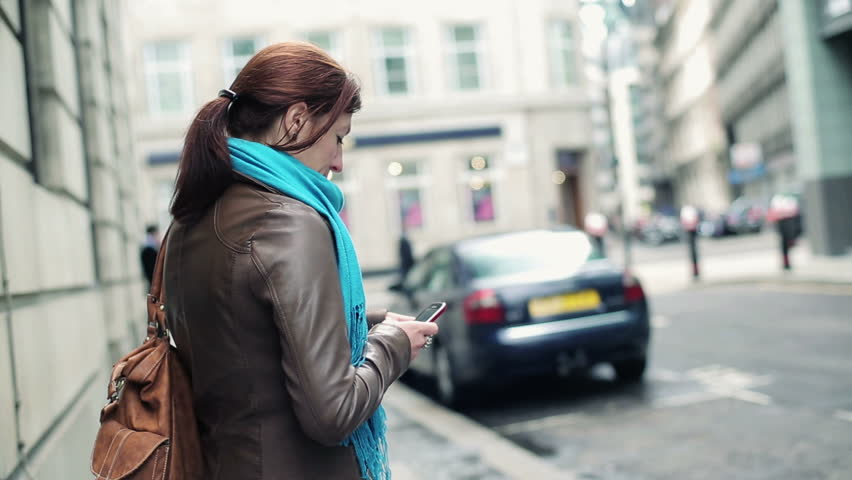 Happy woman with smartphone in the city