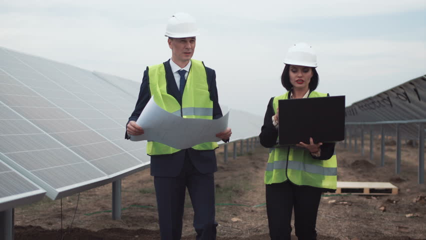 Engineer with tablet pc near the factory episode 3 stock footage the men and woman engineers walking between rows of photovoltaic panels with blueprint between row of malvernweather Image collections