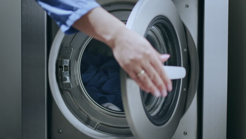 Loading washing machine. Load clothes to washer machine. Female hand put uniform in laundry machine. Load clothes laundry washing machine. Preparing laundry washing