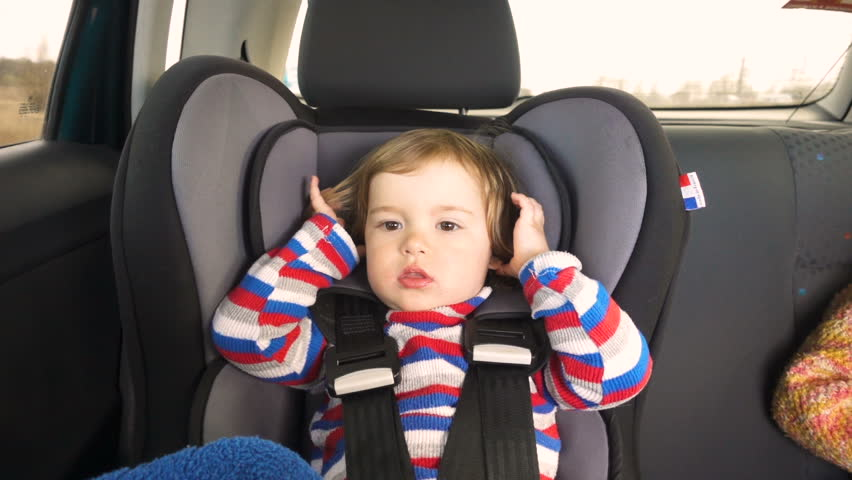 boy baby kid in a striped jacket in the childrens car seat in the car rides