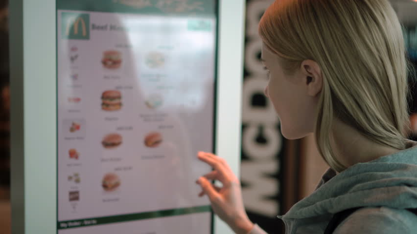 DUBAI AIRPORT, UAE- CIRCA MARCH 2017: Woman ordering food via self-service machine at Mcdonald's