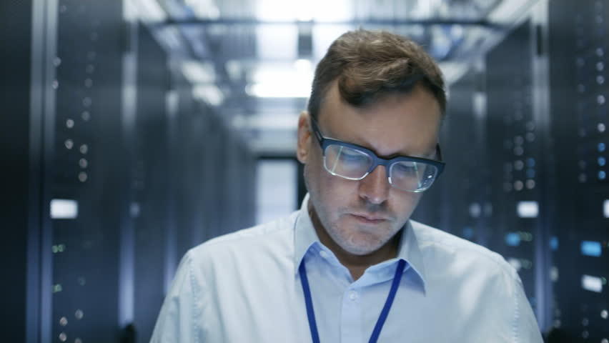 Follow-up Shot of IT Technician Walking Through Data Center. Rows of Working Server Racks are Visible and Have Blinking LED Lights. Shot on RED EPIC-W 8K Helium Cinema Camera.