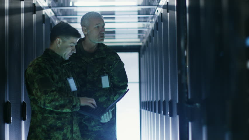 In Data Center Two Military Men Work with Open Server Rack Cabinet. One Holds Military Edition Laptop. Shot on RED EPIC-W 8K Helium Cinema Camera.