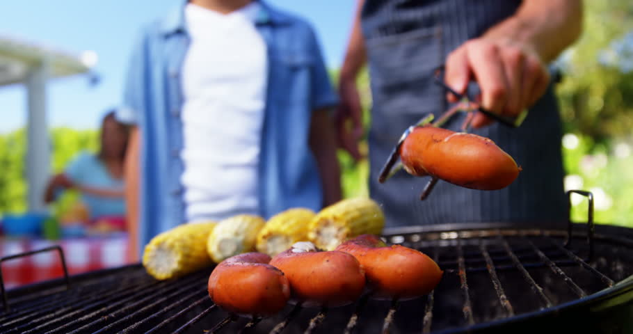 Father and son grilling sausages and corns on barbecue in the house garden | Shutterstock HD Video #26009936