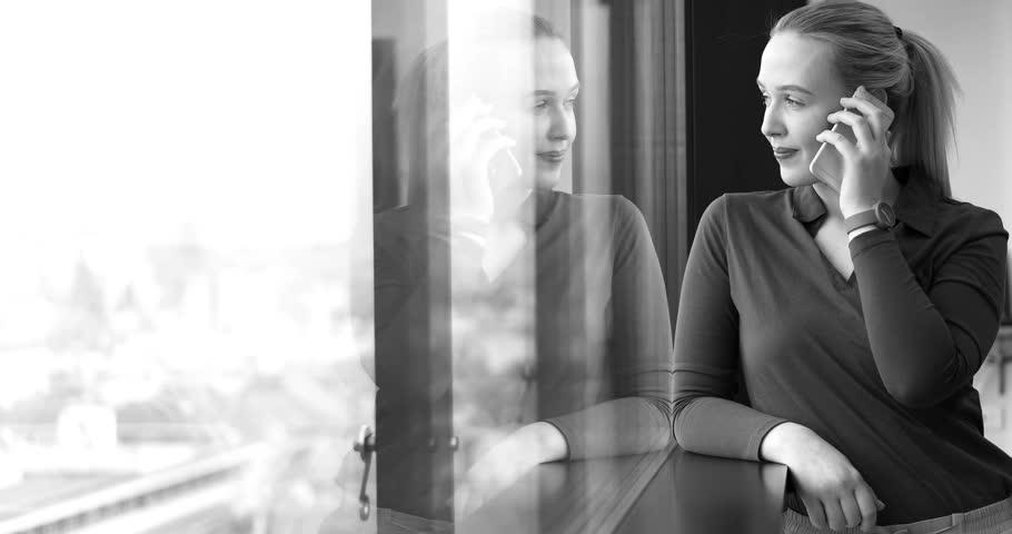 Elegant Woman Using Mobile Phone by window in office building | Shutterstock HD Video #26012336