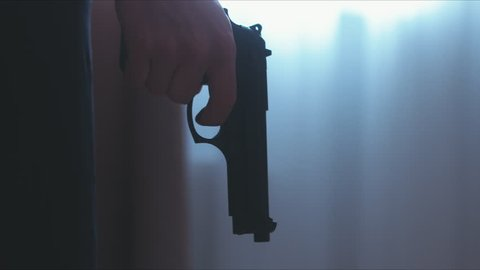 LR DOLLY Silhouette of male criminal pulling back the hammer of a pistol near the window. 4K UHD RAW edited footage