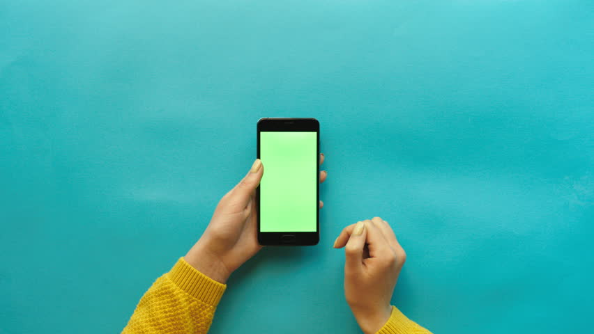 Woman using smart phone with green screen on blue table background. Female hands scrolling pages, tapping on touch screen. top view. Chroma key. Creative background