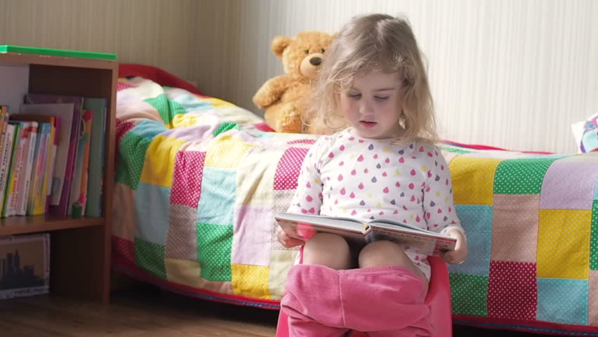 Toddler Girl Sitting On A Potty And Reading Book Stock