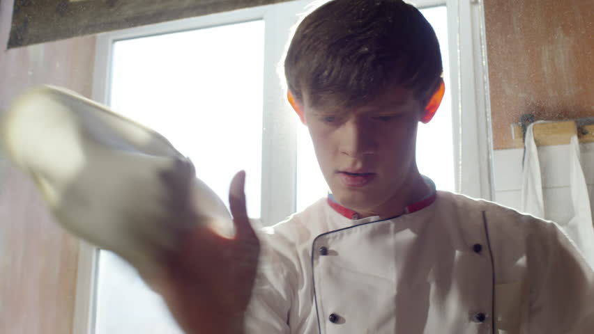 Closeup of young pizzaiolo spinning pizza dough on fingertip and throwing it up in sunny restaurant kitchen. Slow motion footage