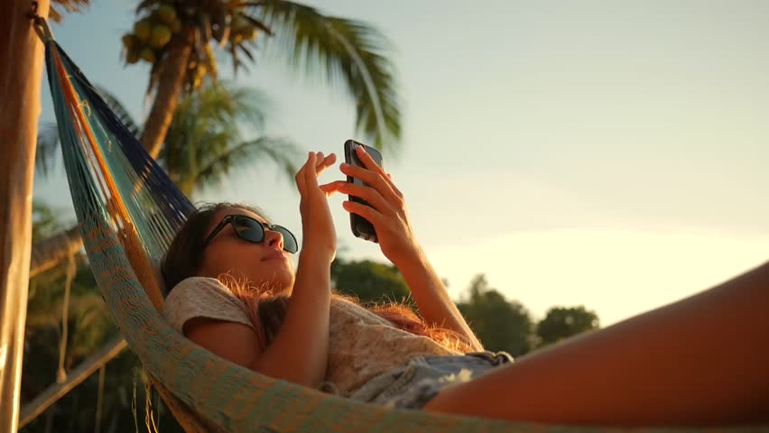 Relaxed Mixed Race Young Woman Looking at Mobile Phone in Hammock at the Beach near the Sea at Sunset. Koh Phangan, Thailand. HD Slowmotion. | Shutterstock HD Video #26088971