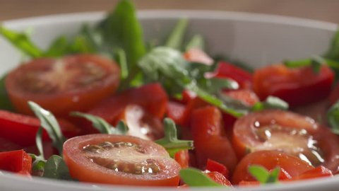 Slow motion of dressing with olive oil fresh salad with arugula, cherry tomatoes and paprika closeup, 180fps prores footage