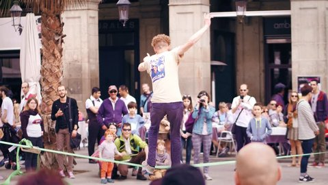 BARCELONA, SPAIN - APRIL, 16, 2017. Tightrope acrobat performing in the street. Balancing on a swaying strap. 4K video