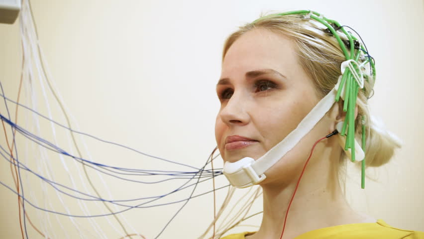 Electroencephalographic examination. Female patient sitting in the hospital room and doctor neurologist monitoring the functions of the brain. HD