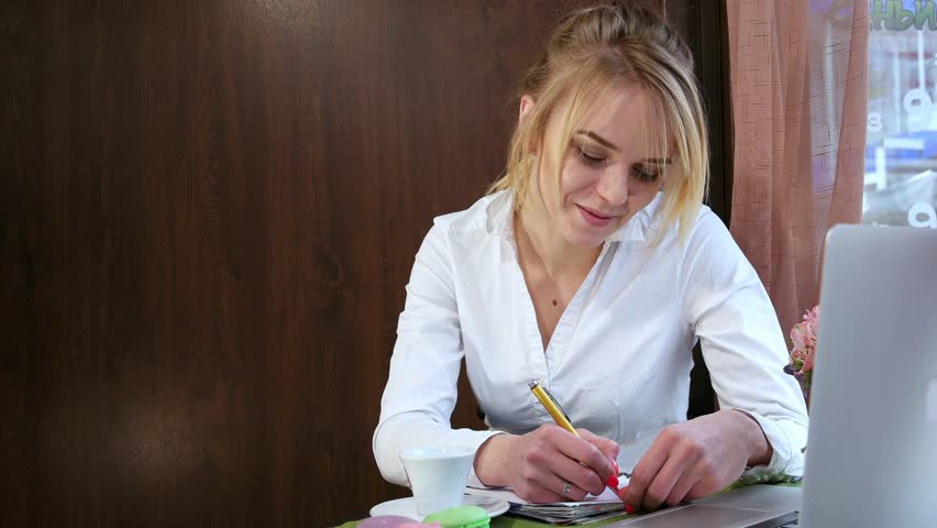 Woman Sits At A Table In Cafe And Making Notes Diary