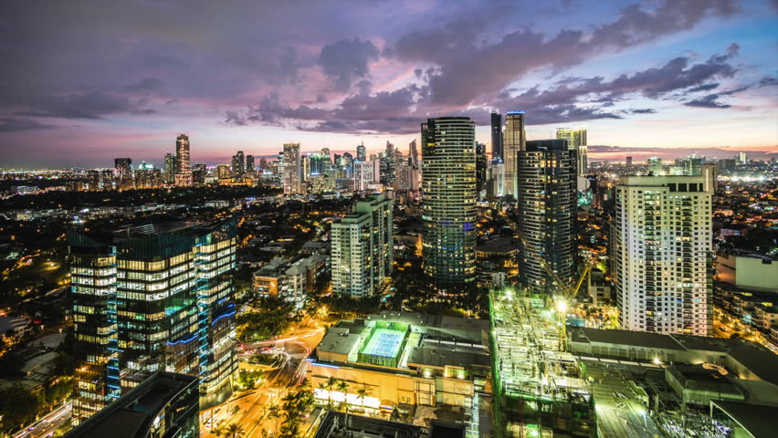 Metro Manila time lapse, looking over Makati city skyline at sunset, Philippines - zoom in.