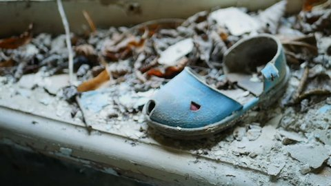 Children's sandal on the windowsill of a ruined house in the abandoned city of Pripyat after the tragedy at the Chernobyl nuclear power plant. Conceptual video about child missing or kidnapping