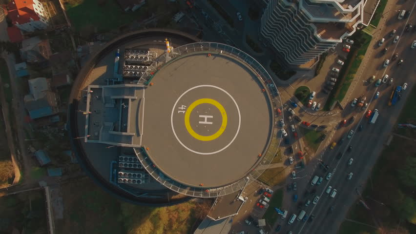 POW above top view modern business center with helipad 4K UHD aerial footage