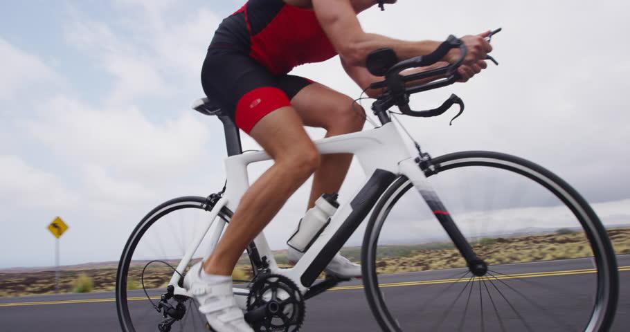Triathlon biking - male triathlete cycling on triathlon bike. Fit man cyclist on professional triathlon bicycle wearing time trail helmet for ironman race.