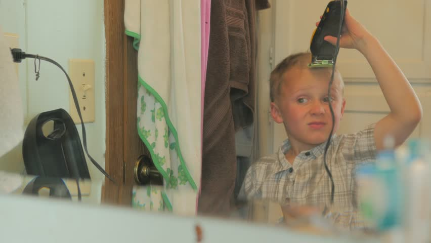 Buzzing his own hair, this little boy got into the trimmers by himself and is ruining his hair.