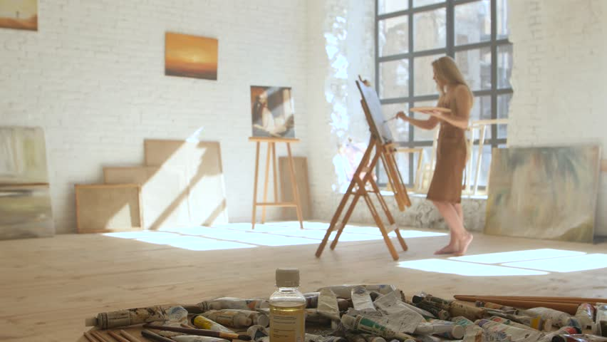 Girl artist paints on canvas on easel and holds palette in art workshop