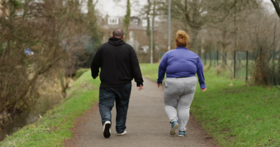 4K Obese couple walking away from camera, smoking cigarettes outdoors in the park. Social issues, unemployment & unhealthy lifestyle concept. Slow motion.