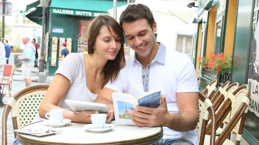 Couple on a coffee shop terrace reading tourist book