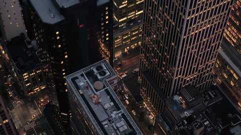 AERIAL HELI SHOT, CLOSE UP: Flying above the rooftops of skyscrapers, office buildings and blocks of flats in Midtown Manhattan, New York City in the early morning near Bryant Park and the 6th ave