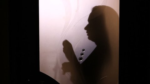 Silhouette of a woman changing clothes behind a glass door. She takes off her underwear