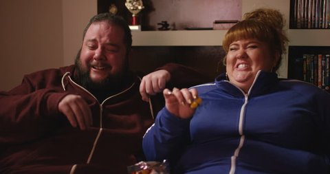 4K Overweight couch potato couple eating junk food & watching something funny on TV