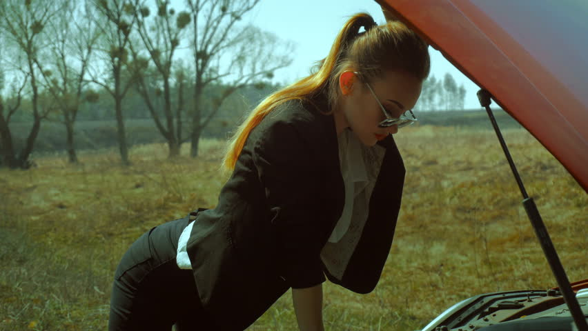 Hot blonde girl in sunglasses looks under the hood of the red car outdoors in the field | Shutterstock HD Video #26232566