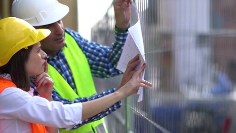 Two civil engineers holding plans and inspecting the construction site among scaffolding