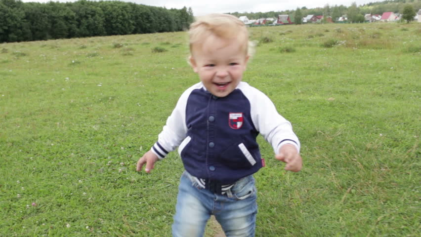 The one year old cute fair-head boy is making his first steps