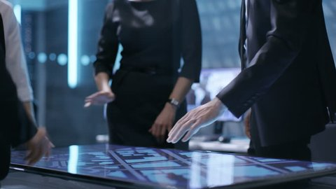 Close-up of Surveillance Agency's Agents Hands on Interactive Touchscreen Table, Tracking Dangerous Criminal. They're in Hi-Tech Monitoring Room. Shot on RED EPIC-W 8K Helium Cinema Camera.