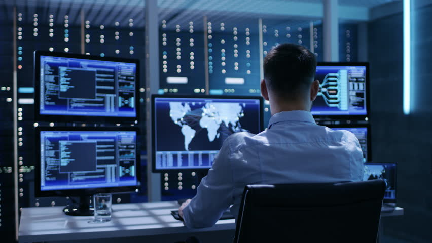 Technical Controller Working at His Workstation with Multiple Displays. Displays Show Various Technical Information. He's Alone in System Control Center.  Shot on RED EPIC-W 8K Helium Cinema Camera. | Shutterstock HD Video #26262956