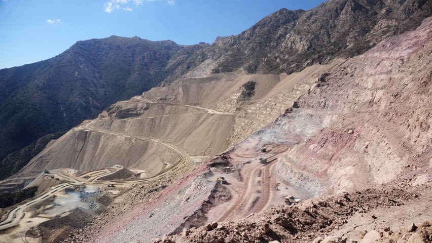 Heavy equipment digs and hauls ore inside an enormous open pit mine. Chile. Timelapse, Two shots