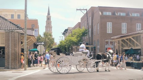 CHARLESTON, SC - APRIL 15: Horse drawn carriages and pedestrians walk the streets of downtown Charleston, South Carolina on April 15, 2017.