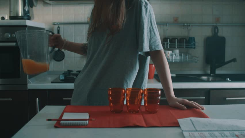 Unrecognizable sluggish brunette girl in grey shirt pouring orange juice out of jug into red glass on kitchen table with notebook and calendar, spills it everywhere