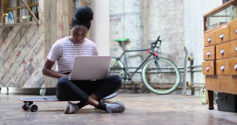 Young adult female sitting on skateboard using laptop