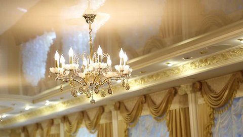 Luxury bright interior. Closeup of chandelier hanging from stretch golden color ceiling in living room. Windows decorated with beautiful draped curtains. Camera moves from left to right.