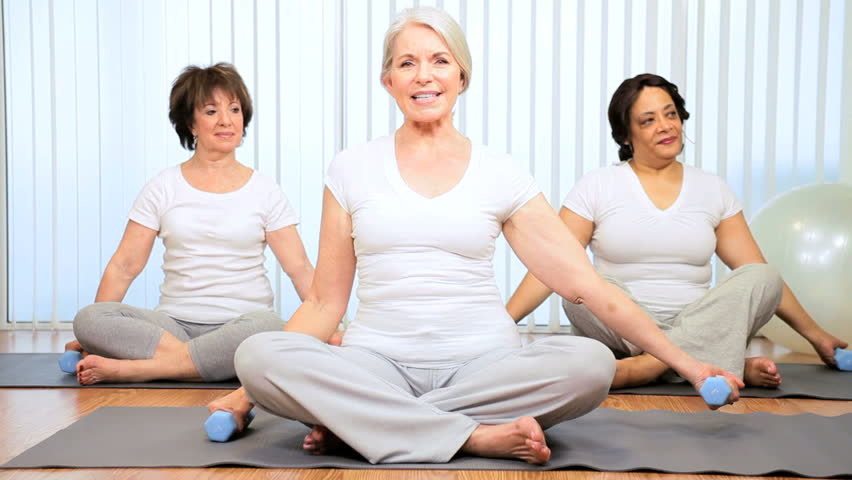 Older Caucasian female instructor teaching yoga to senior ladies