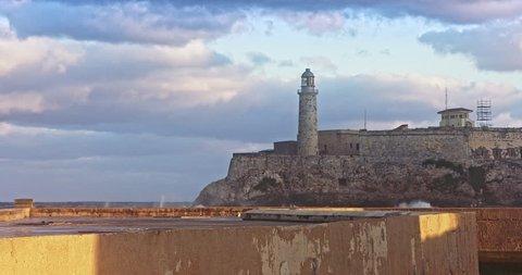 wave crashing on malecon with the Faro Castillo del Morro lighthouse