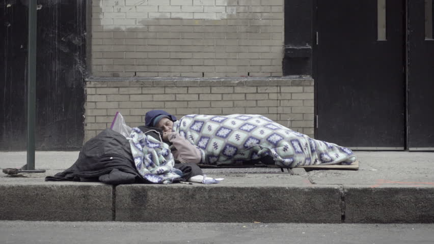 NEW YORK - MARCH 9, 2017: Homeless Woman Sleeping On Sidewalk In Street Windy Winter 4K NYC. Common reasons for homelessness in NYC include: eviction; overcrowded housing; domestic violence; job loss.